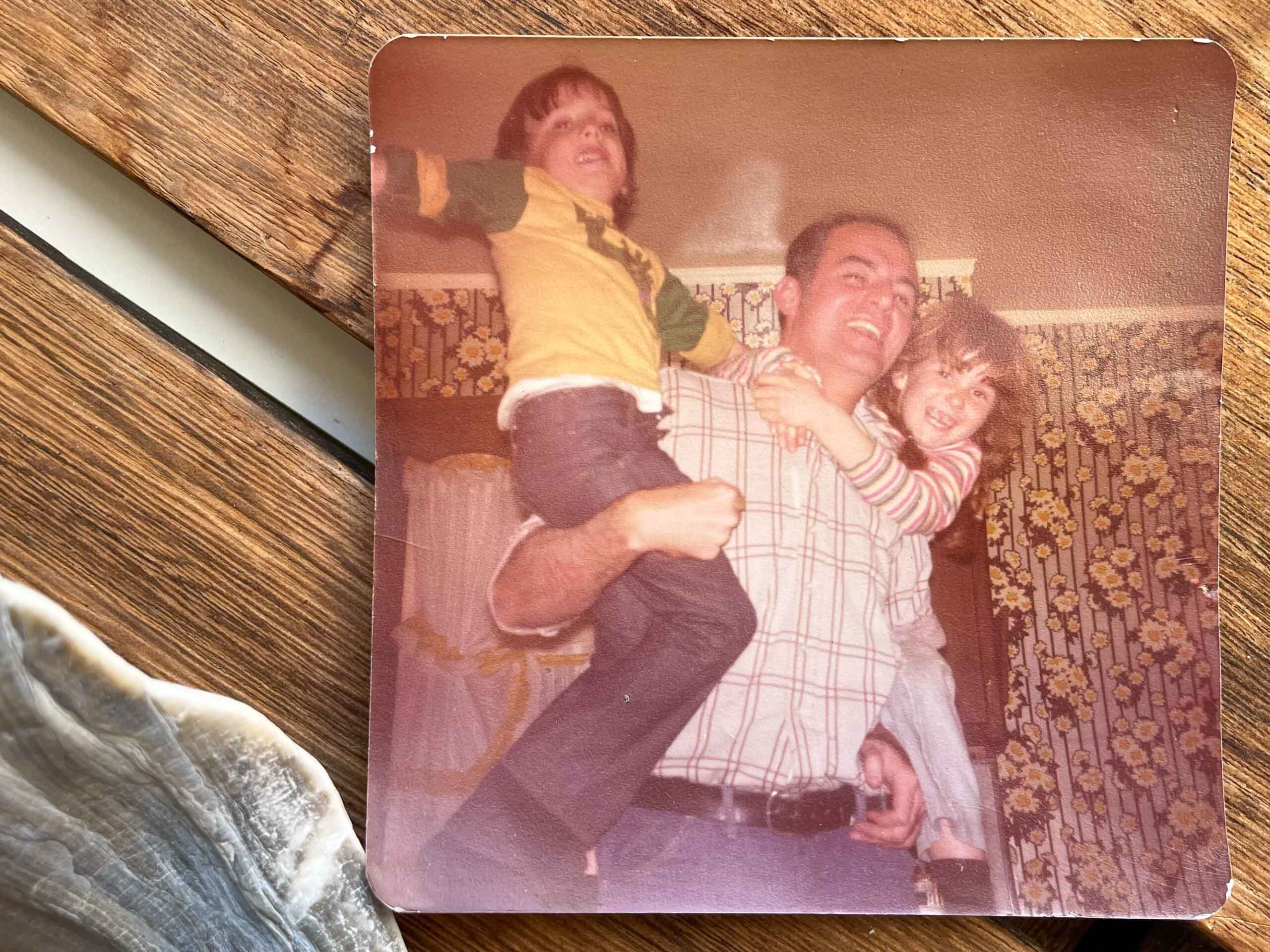 Tall Dad holding laughing kids in a kitchen in Brooklyn with seventies flowered wallpaper