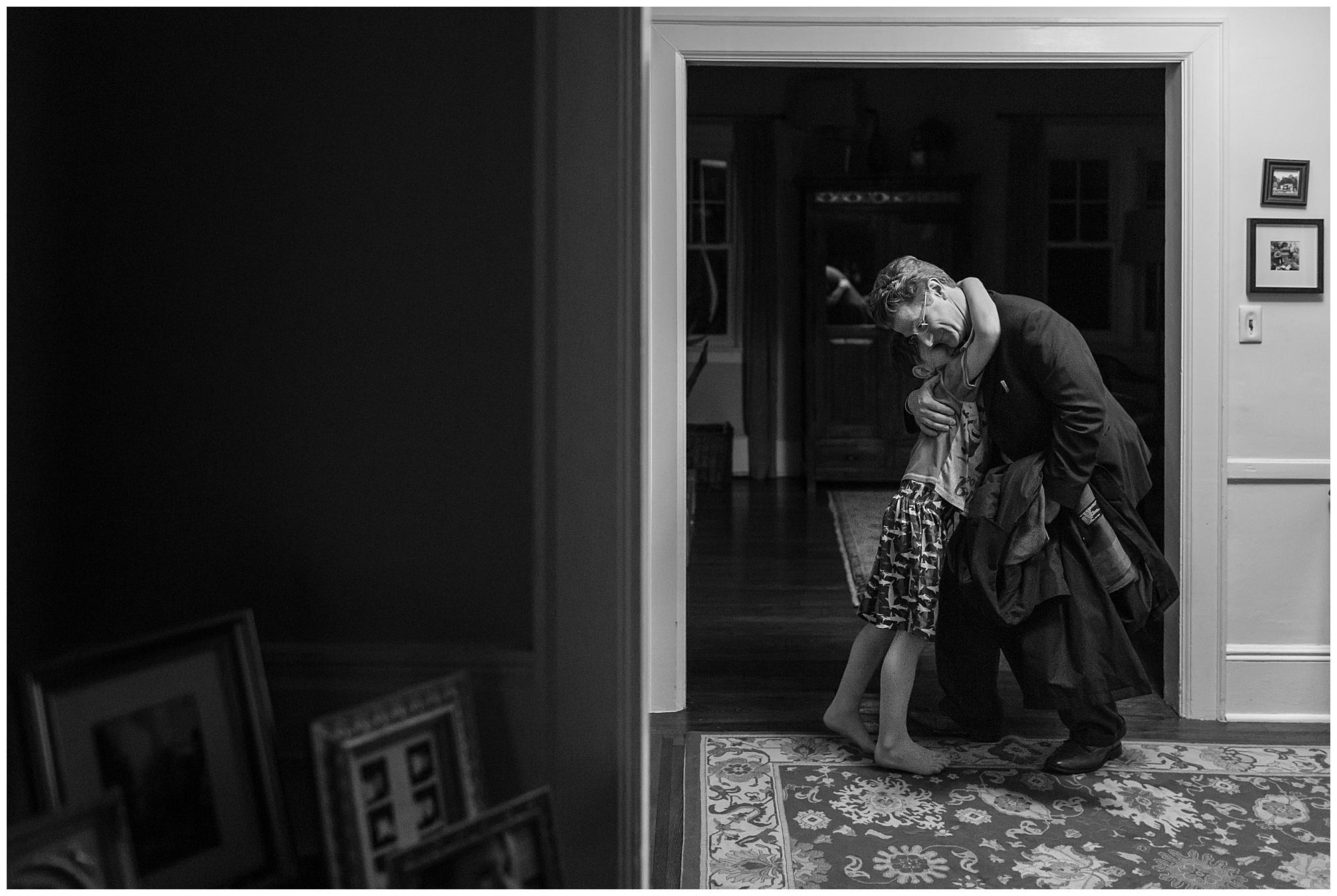 Little boy greets dad in hallway after work.